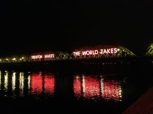 Photograph of the Lower Trenton Bridge. The slogan Trenton Makes, the World Wakes is illuminated on the side.