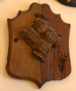 a color photograph of the Contributionship's fire mark, wooden shield with a bronze