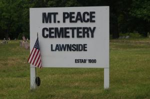 "Color photograph depicting white sign that reads ""Mount Peace Cemetery Lawnside Established 1900."" An American flag is next to the sign. Graves are visible in the background."