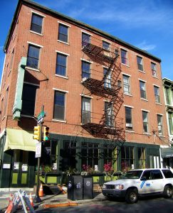 Color photograph showing a brick building with a simple iron fire escape. The ground level of the building has a storefront with many plants.