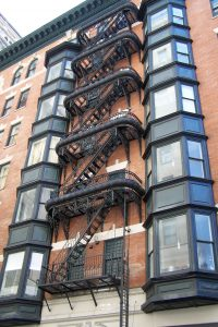 Color photograph showing a fire escape decorated with ornate metalwork.