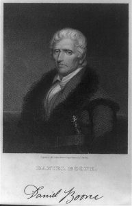A black and white illustration of Daniel Boone wearing a coat with fur on the collar and lapels. He has an elaborate hunting knife tucked into his belt.