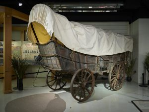 A color photograph of a conestoga wagon with wooden frame and wheels and a cloth cover. The wagon is on display inside of a museum setting.