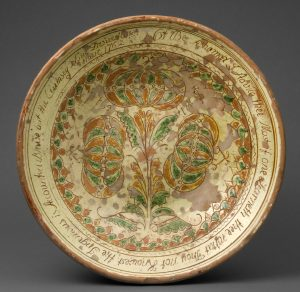 Close up picture of a plate with plants painted on it, and writing along the rim.