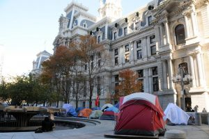 Color photograph depicting many tents pitched outside of Philadelphia City Hall.