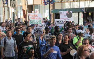 Color photograph showing a crowd of protesters, some holding signs, some with instruments, and some chanting.