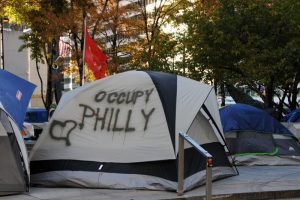 Color photograph showing a camping tent. Spray painted on the side of the tent is Occupy Philly and a heart.