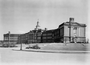 A black and white photograph of a large school building with greek-style columns at the front entrance and a tall white cupola on top.