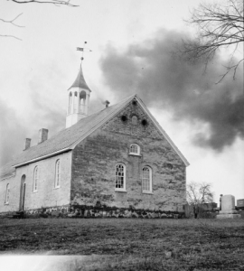 a black and white photograph of a small stone church with arched windows. The roof is topped by a white steeple with a weather vane. There is a small graveyard next do it. The photograph is taken in winter and several leafless trees stand in the background.