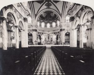 A black and white photo of the interior of the St. Joseph's Church in South Camden, New Jersey. The photograph is taken from the rear of the church down the central aisle, showing rows of pews and arched galleries along the walls. At the front of the church is an alter adorned with religious statues, housed in a domed alcove with an ornately detailed ceiling.