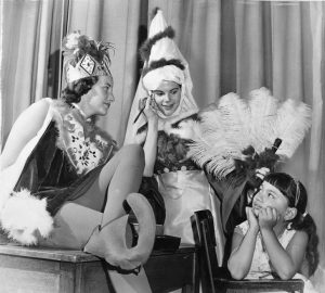 Black and white photograph of young women in fantasy costumes doing make up while a child looks on.