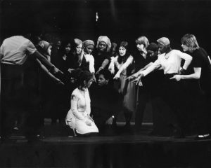 Black and white photograph showing a group of actors huddled around and a seated couple and pointing at them.