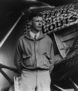 Charles A Lindbergh standing next to his monoplane, the Spirit of Saint Louis.