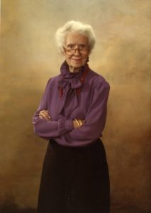 Color portrait of Maggie Kuhn. She is wearing a purple blouse, black skirt, and a red necklace.
