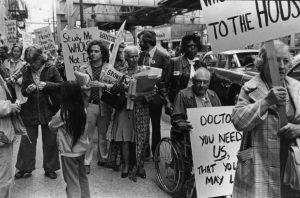 Black and white photograph of a crowd of people holding protest signs.