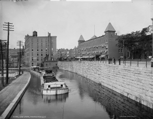 A black and white photograph of barges traversing the Erie Canal at Rochester, New York. A hotel with a painted sign reading Osburn House and other large buildings line the banks of canal. A group of men stands by the edge of the canal watching the barges.