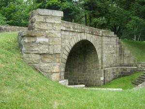 A color photograph showing a stone arch bridge. The stones on the arch are laid on an angle to support the uneven landscape of the area. The bridge stands in a grassy park with a stand of trees in the distance.