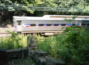 A color photograph of a low, unmarked stone memorial in the grassy edge of a wooded area. Behind it, a SEPTA train passes at high speed.