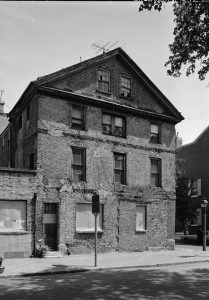 A black and white photograph of the Thaddeus Kosciuszko house. The three story brick home is in a state of disrepair with boarded windows, crumbling bricks, and evidence of previous repairs. A historical marker stands in front of it.