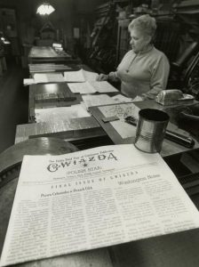 "A black and white photograph of a newspaper printing room. A woman stands reading a paper set on a desk. In the foreground, a folded newspaper reads ""GWIAZDA. Polish Star. Final issue of Gwiazda."""