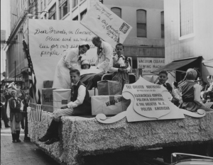 "A black and white photograph of the 1952 Pulaski Day Parade. Adults wearing a doctor and nurse costume stand on a float featuring a hospital bed. A child lays in the bed with bandages on her head and other children sit on boxes labeled ""medical supplies,"" ""penicillin,"" and ""vaccines"". In the background, a giant letter and envelope give a plea for medical supplies."